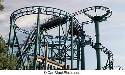 Red roller coaster running in its tracks containing people...