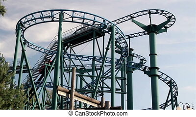 Red roller coaster moving upwards afternoon - Red roller...