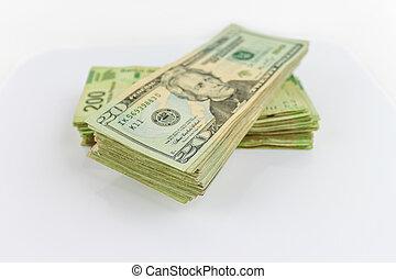 Cash - A stack of Us dollars bills and Mexian Pesos bills.