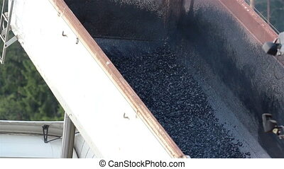 Truck carrying asphalt attached to asphalt paver as the...