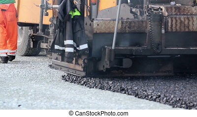 Asphalt paver applying asphalt on the highway. An equipment...