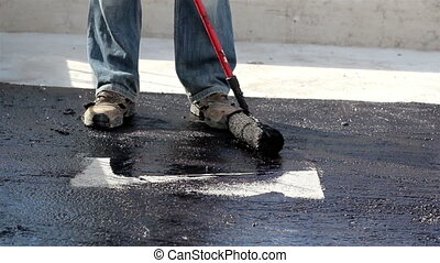 Road men manually applying asphalt on the highway after the...