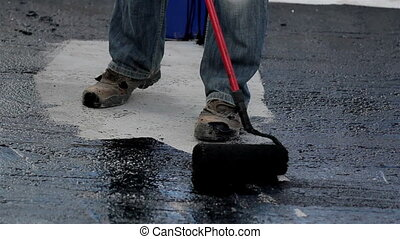 Road men applying asphalt on the small part of the highway...