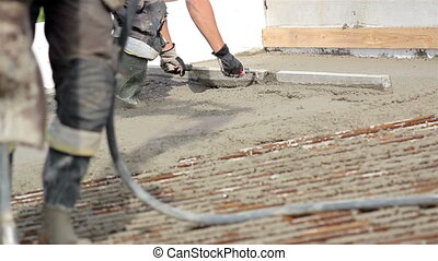 Men wearing working boots and head gear is flattening cement...