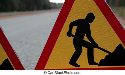 Men working road sign at the side of the road to indicate...