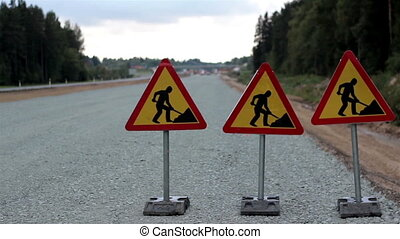 Men working sign in the highway and cars passing on the other side