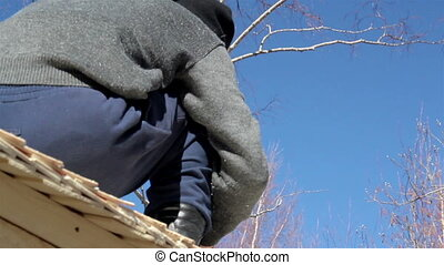 Man roofer working Cedar wooden shingles roof roofing...