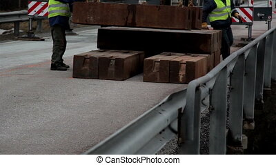 Heavy blocks equipments of wood are carried and arranged in...