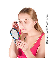 A young woman putting make up on her