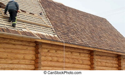 Roofer working on unfinished pine tared cedar wooden shingle roof