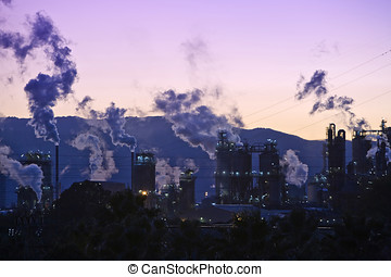 Smoking chimney at sunset on industrial buildings complex, Algeciras, Cadiz province, Andalusia, Spain