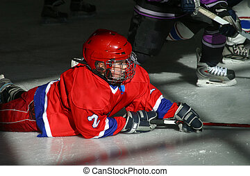 Young hockey players in uniforms play on ice