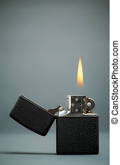 Burning Lighter - black gasoline lighter with flame on dark...