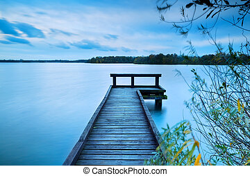 wooden pier on big lake with long exposure