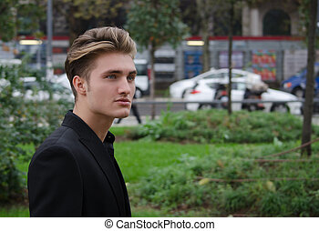 Attractive blue eyed, blond young man outdoors in city