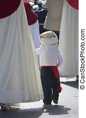 Boy dressed of costalero of his mothers hand during Holy...
