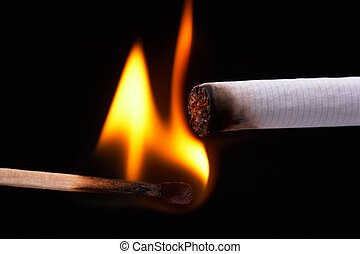 Light a cigarette with a match, black background