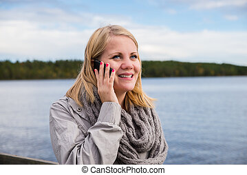young woman talking on the phone and smiling with lake and...