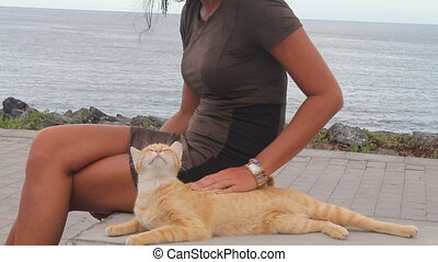 girl stroking a ginger cat