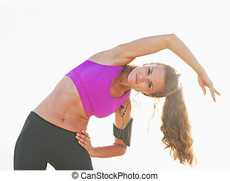 Healthy young woman stretching outdoors