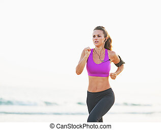 Fitness young woman running on beach