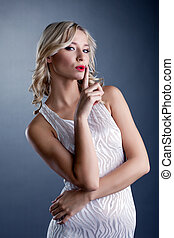 Studio shot of stylish young blonde in white dress