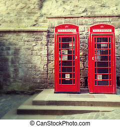 A pair of traditional Britsh red phone boxesagainst the wall...