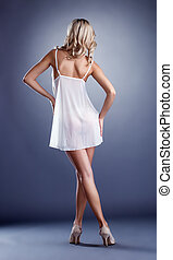 Graceful model posing in negligee back to camera, on gray...
