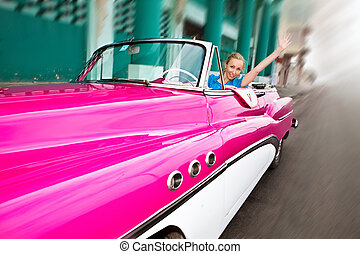 The beautiful woman at a wheel old American retro car (50th...
