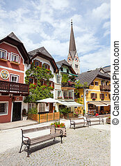 Colorful houses village square in H - Public water fountain...
