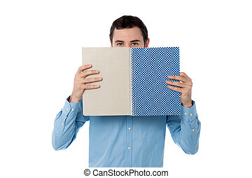 Young man hiding his face with notebook - Handsome guy...