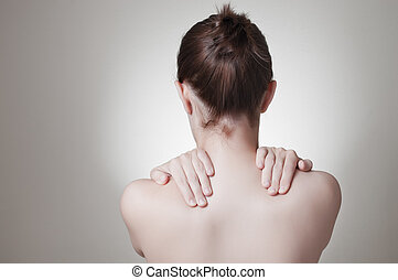 Woman with back pain - Rear view of a young woman touching...