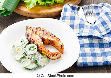 Grilled salmon with cucumber salad on a plate