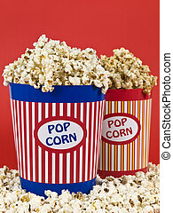 Two popcorn buckets over a red background.