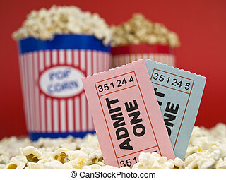 Movie stubs and popcorn - Two popcorn buckets over a red...