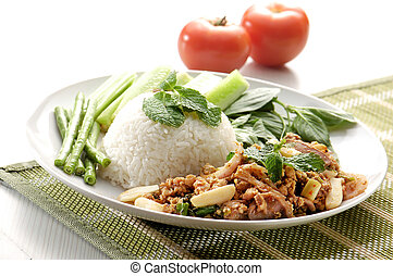 Chicken with rice and vegetables in background