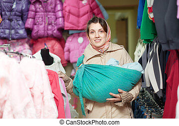 woman with baby in ringsling chooses clothes