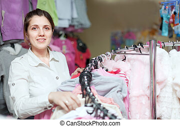 woman chooses blouse at  store