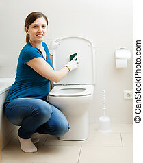 Smiling woman cleaning toilet seat - Smiling woman cleaning...