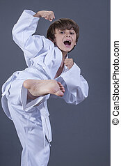 Karate kid - Young handsome Caucasian boy performs side kick...