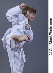 Karate kick - Young handsome Caucasian boy with scared...