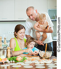 Happy parents with young children dumplings fish cooking in...