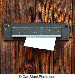 Letter box with envelope on wooden door