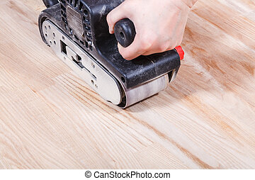 finishing wooden surface by hand-held belt sander -...