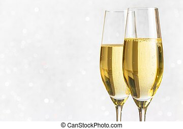 a pair of flutes of golden champagne on silver bokeh...