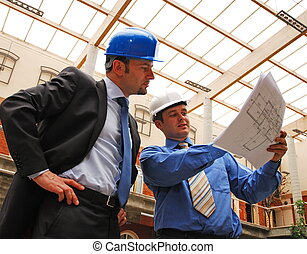 Architects Reviewing Blueprint - Two architects reviewing...