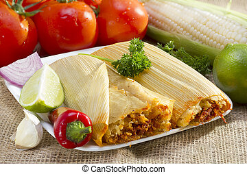 Mexican tamales on plate. - Mexican tamale wrapped in corn...