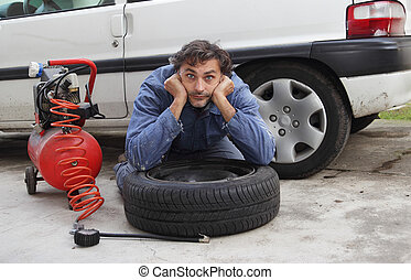 man and tire puncture - Changing a tire, pensive man and...