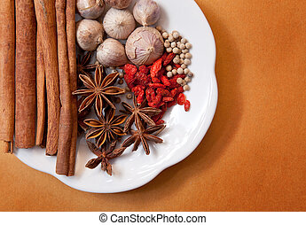 dry asia spice herb vegetable garlic cinnamon stick white pepper dried wolfberry chinese star anise in white ceramic dish