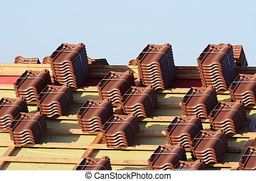 Roof Tiles - Renovation of a house roof with stacks of roof...